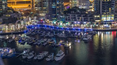 Luxury Dubai Marina canal with passing boats and promenade with restaurants night timelapse, Top view from above with illuminated skyscrapers. Dubai, United Arab Emirates