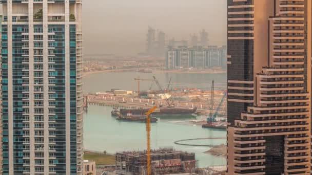 Luftaufnahme von Dubais Marina-Wolkenkratzern mit Baustelle und Palmen-Jumeirah-Insel im Zeitraffer.