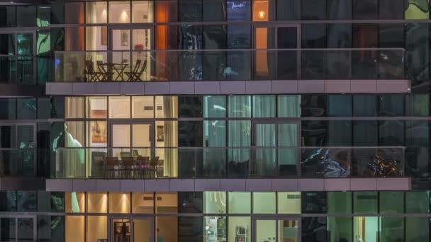 Reihen glühender Fenster mit Menschen in Mehrfamilienhaus in der Nacht.