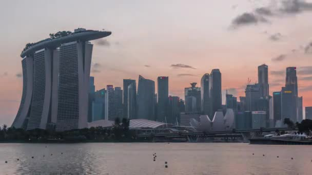 Downtown skyline of Singapore as viewed from across the water from The Garden East day to night timelapse. Singapore.