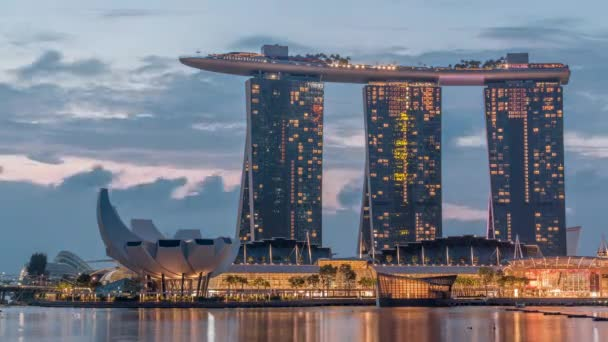 Marina Bay Sands Hotel dominates the skyline at Marina Bay in Singapore night to day timelapse.