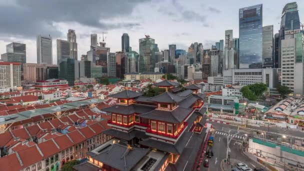 The Buddha Tooth Relic Temple comes alive at night in Singapore Chinatown day to night timelapse, with the city skyline in the background.