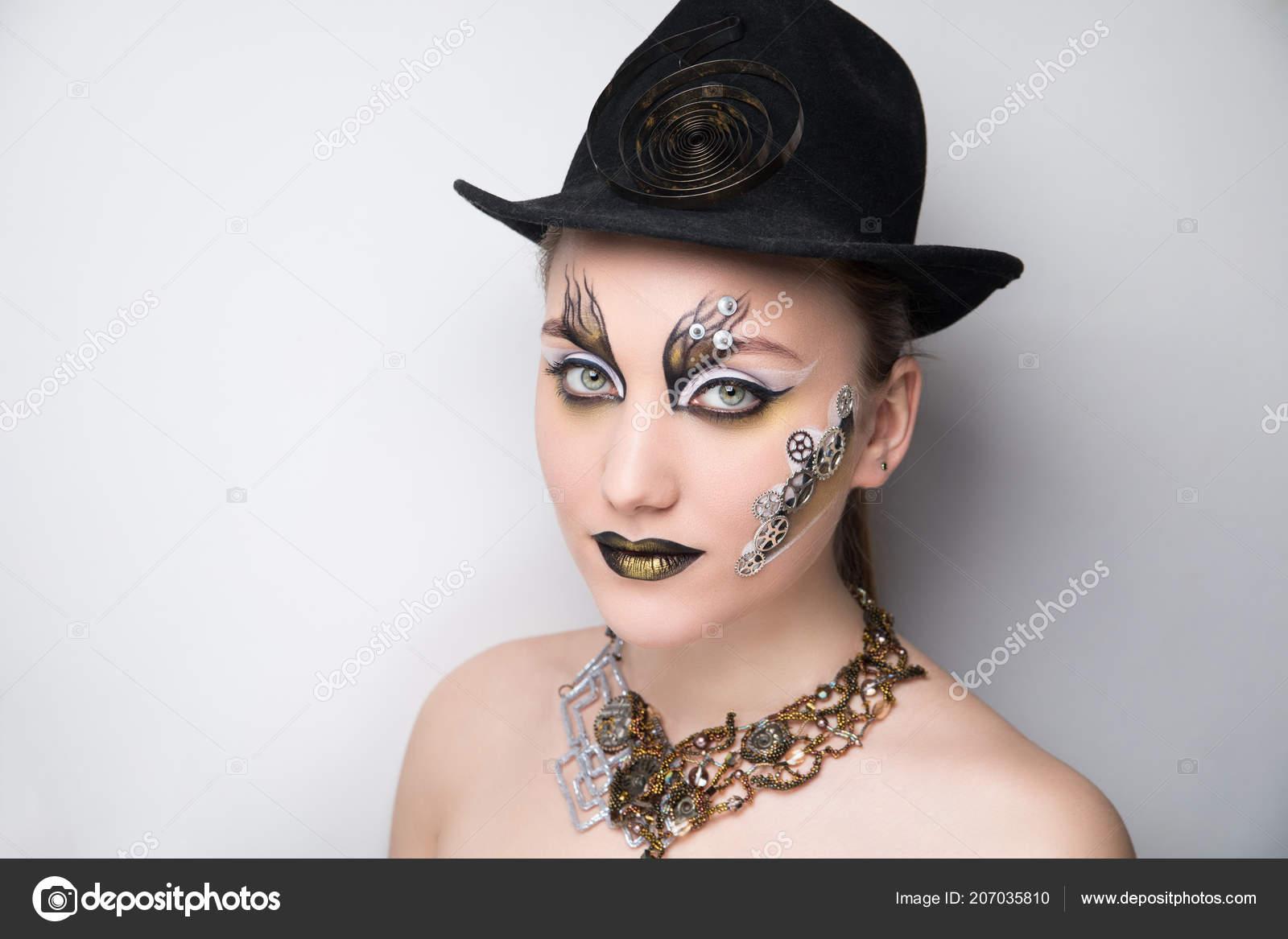 Retrato de una mujer hermosa steampunk sobre fondo gris. Sombrero negro  accesorio vintage con resorte de reloj del metal. Gran collar de oro plata. 27d68ecf85f