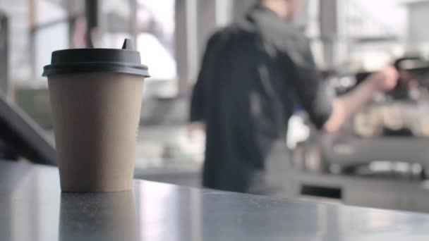 Sklenici kávy u baru. Rozmazané pozadí. Barista připravuje šálek kávy pro zákazníka v kavárně.