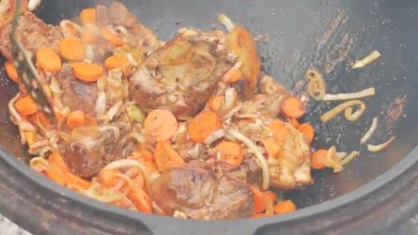 Opravdový uzbecký pilaf v obrovském kotlíku. Vaření národních jídel. Tradiční vaření pilaf. Příprava národních jídel