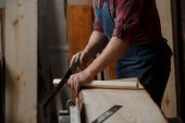 Photo Master carpenter saws board with hacksaw in workshop. Close up