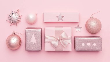 Pastel pink minimal christmas banner. Beautiful nordic christmas gifts isolated on pastel pink background. Pink colored wrapped xmas boxes composition.