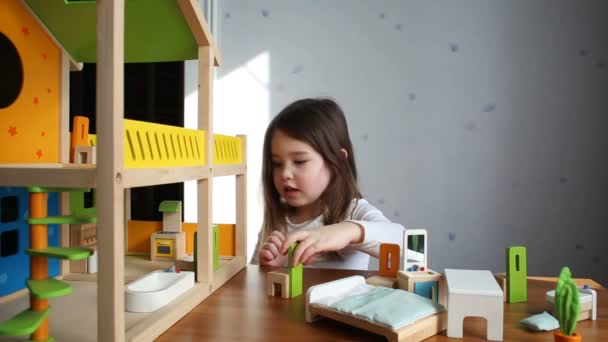 A cute girl playing with her dollhouse