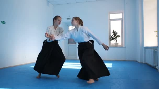 Two girls in black hakama practice Aikido