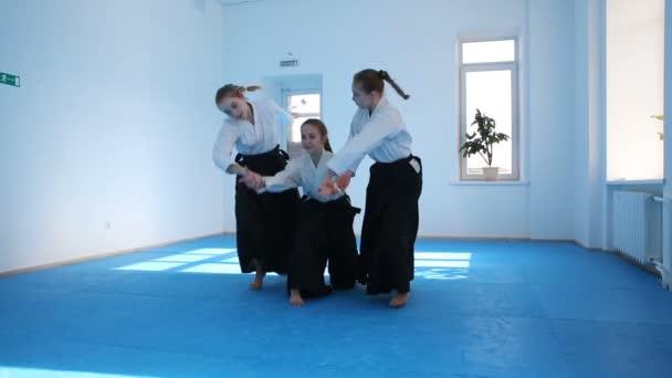 Three girls in black hakama practice Aikido