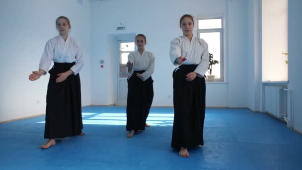 Three girls in black hakama practice Aikido movements on martial arts training