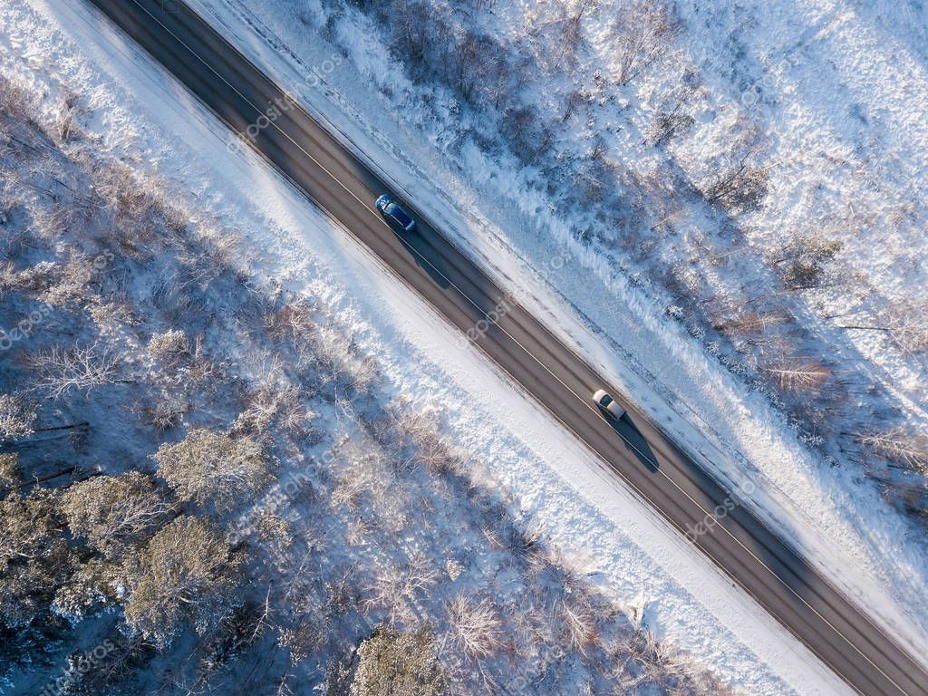 Cars on road in winter with snow covered trees aerial view