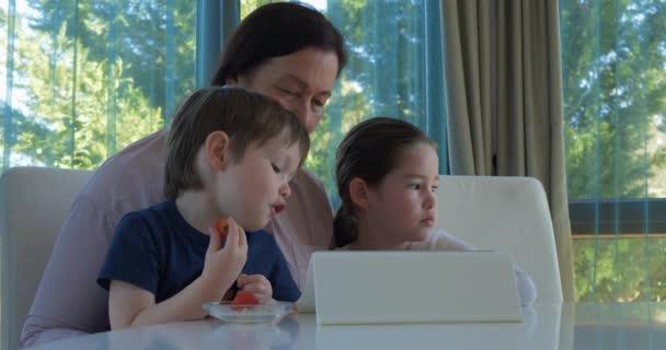 Babička baví její malá vnoučata s tabletu počítačová hra