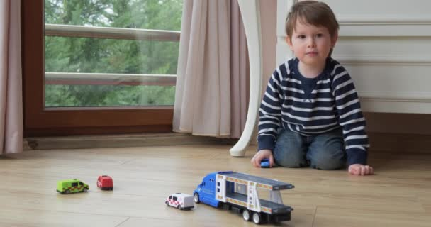 Toddler boy plays with cars a home