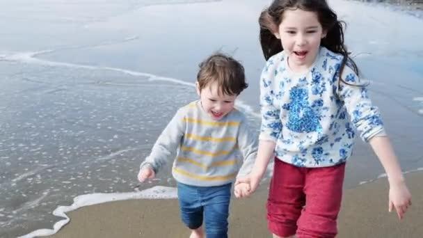 Šťastné děti hrají na pláži. Sestra a její bratříček se drželi za ruce