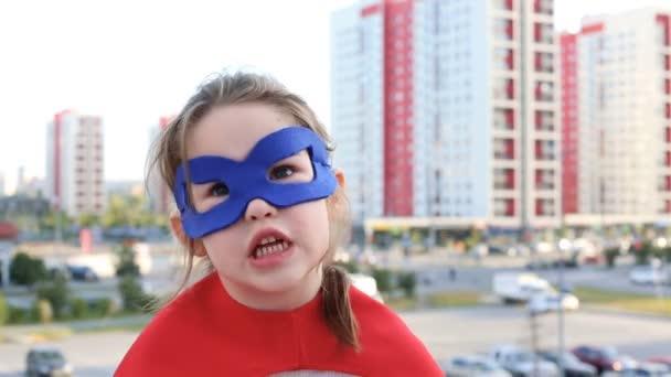 Ragazzino di supereroe contro fondo urbano
