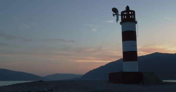 Malý maják na nábřeží s výhledem na hory při západu slunce