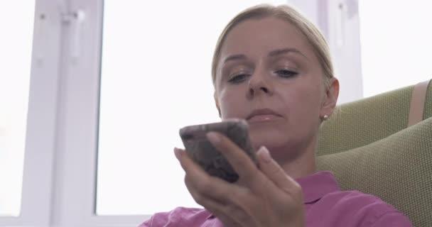 Szőke nő használ egy okostelefon hangfelismerő funkció online