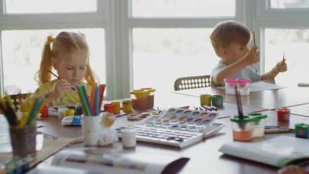 Chlapec a dívka se učí kreslit v předškolní skupiny
