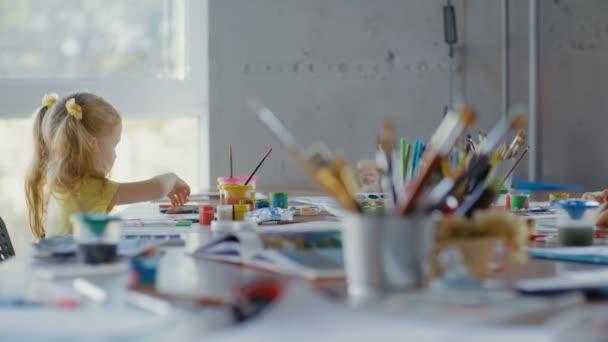 Malá holčička kreslí školku. Lekce kreslení pro děti předškolního věku
