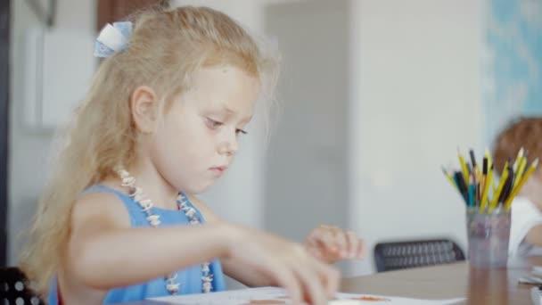 Roztomilá holčička v modrých šatech formy z plasticinu ve školce.