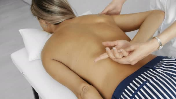 The orthopedist doctor does a backbone massage to a young woman. View from the side, the middle plan.