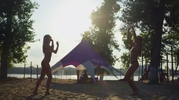 Ženský volejbal hráči, kteří hrají volejbal na pláži