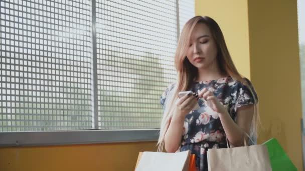 Fiatal ázsiai nő, bevásárló táskák, használ a smartphone.