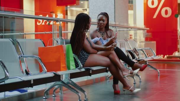 Africká žena mluví a kontrolu smartphone po nakupování v nákupním centru.