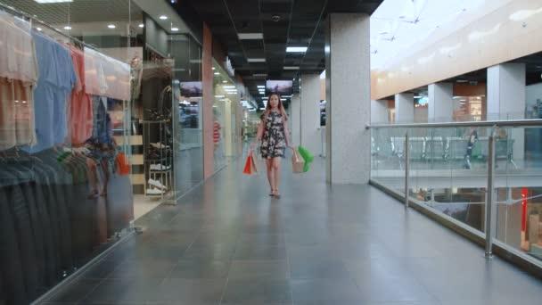 Mladá asijská dívka chůze v nákupním centru s nákupními taškami.
