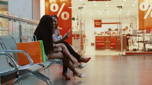 Az afrikai nők a padon ülnek a plázában..