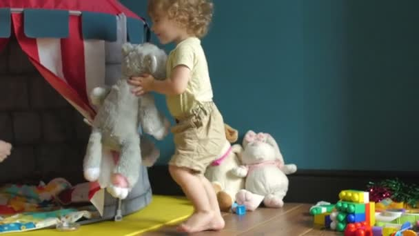 Little cute girl playing soft toys and toy house