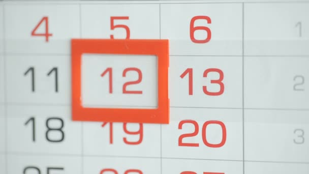 Womans hand in office changes date at wall calendar. Changes 12 to 13