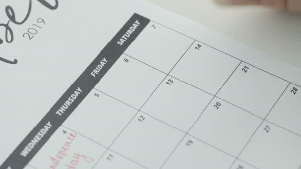 Frauenhandschrift mit rotem Stift auf Kalenderwort Sex