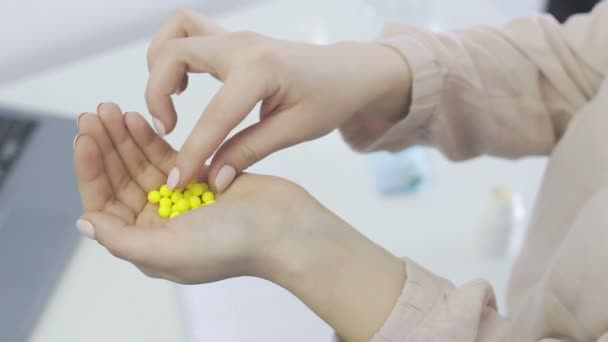 Young woman holding many small and yellow pills, taking one pill into mouth
