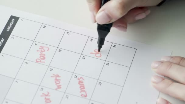Womans hand writing with red felt pen on calendar word date