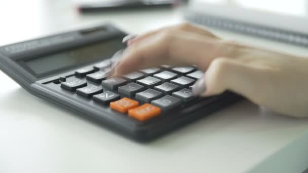 Close up of woman hand using calculator.
