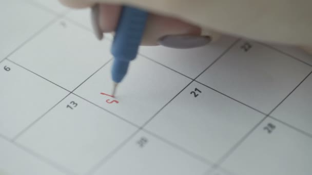 Womans hand writing with red pen on calendar word shopping