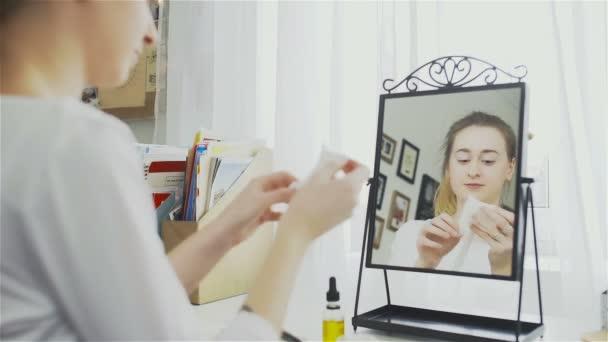 junge Frau beim Öffnen einer Gesichtsmaske. junge Frau macht eine kosmetische Maske für die Hautpflege.
