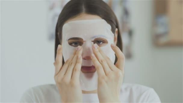 Žena použití kosmetické masky na obličeji a při pohledu na fotoaparát
