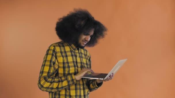 Afroameričan píše na notebooku. Ne od Shaking Head. Na oranžovém pozadí. Pojetí emocí