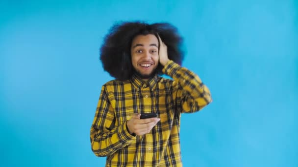 Junger glücklicher afrikanischer Geschäftsmann telefoniert und bekommt gute Nachrichten auf blauem Hintergrund. Konzept der Emotionen