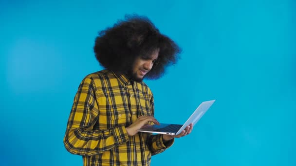 African American man typing at laptop. No by Shaking Head. On Blue background. Concept of emotions