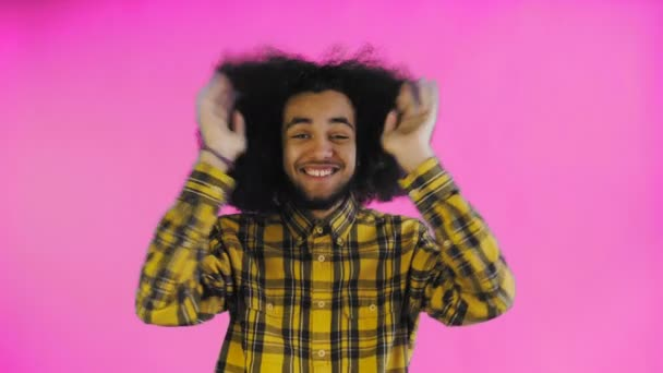 Worried Afro-American Man laughing, keeping hands at her face and Celebrating Success on purple Background.