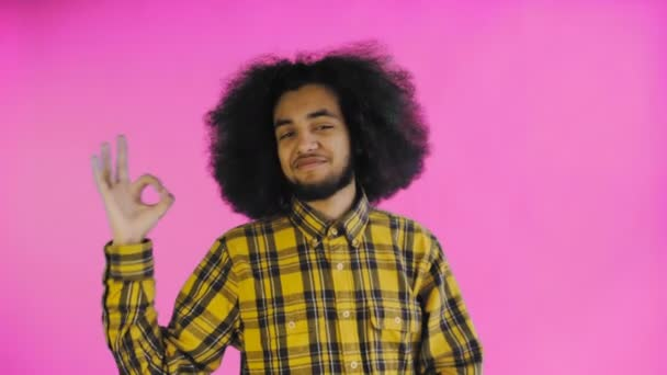 Smiling attractive Afro-American guy showing ok gesture while standing isolated over purple background. Concept of emotions