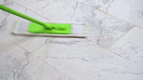 Žena čištění bílé podlahy se zeleným mikrovláknem mop