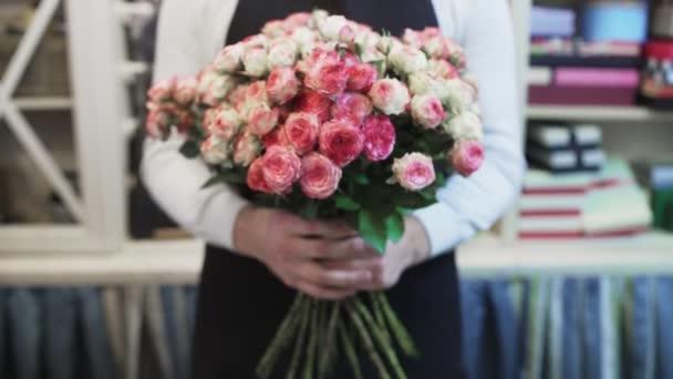 Muž květinářství s velkou kytici růží