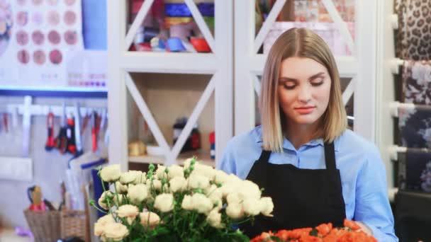 Mladá žena květinářství mluví se zákazníkem