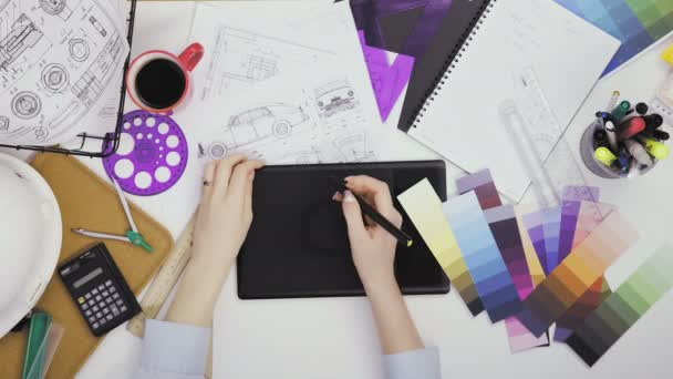 Creative designer using graphics tablet while working at her table