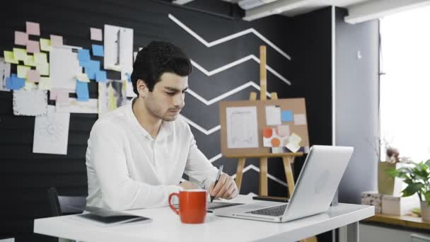 Casual male designer drinking coffee and using graphics tablet in a modern office